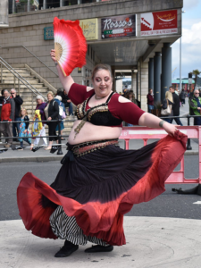 Dancer with a fan in her right hand holding her skirt in her left hand