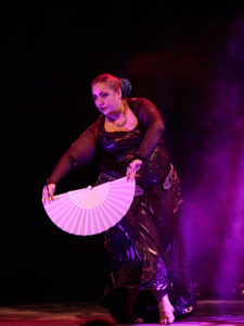 Ana performing at Gothla 2019; dark costume, holding an open white fan