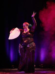 Ana at Gothla 2019's Main Show, wearing a dark shiny costume over a dark background, holding a white fan