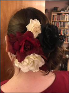 Side chignon with white and red roses, shot from behind